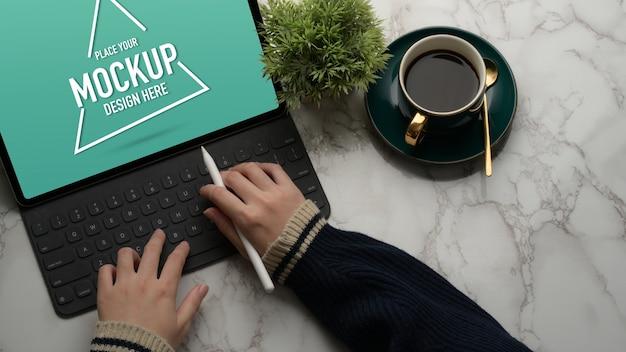Hände, die auf modell digitales tablett auf marmortisch mit kaffeetasse und pflanzentopf tippen