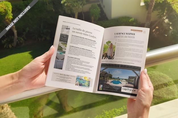 Hände, die broschüren- oder zeitschriftenmodell halten