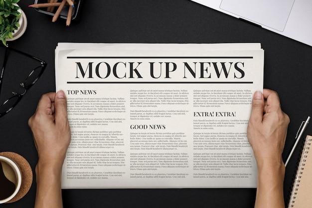 Hände, die geschäftszeitung mit kopierraum-modellschablone auf schwarzer schreibtischoberansicht halten