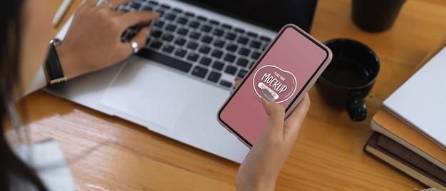 Hände sms auf modell smartphone während der arbeit mit laptop