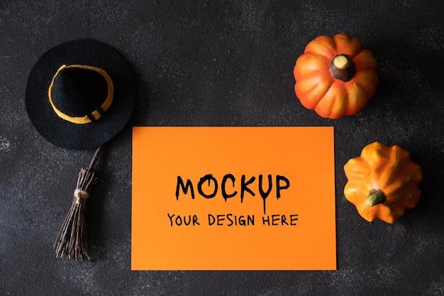 Halloween-grußkarte mit kürbissen und dekorativen hexenattributen auf dunklem hintergrund. flache lage, ansicht von oben. orange leeres papier für halloween-feiertagskonzept.