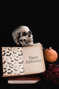 Halloween-konzept mit dem schädel und buch auf schwarzem hintergrund