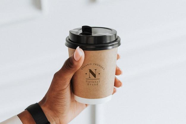 Hand, die ein kaffeetassenmodell hält