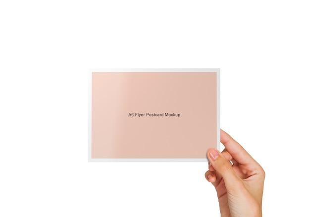 Hand, die ein postkarten-modell hält