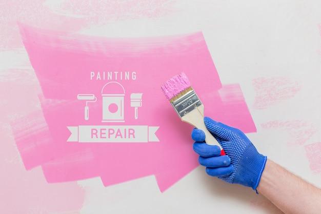Hand, die einen pinsel mit rosa farbe hält