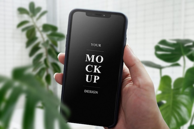 Hand, die mobiles modell nahe grünen blättern hält