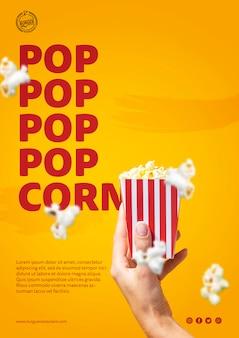 Hand, die popcorntaschenschablone hält