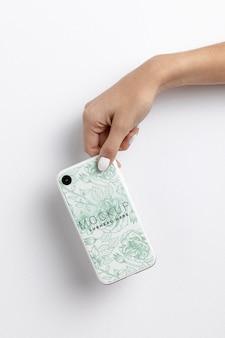 Hand, die smartphone mit abdeckungsmodell hält