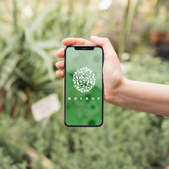 Hand, die smartphonemodell mit gartenarbeitkonzept hält
