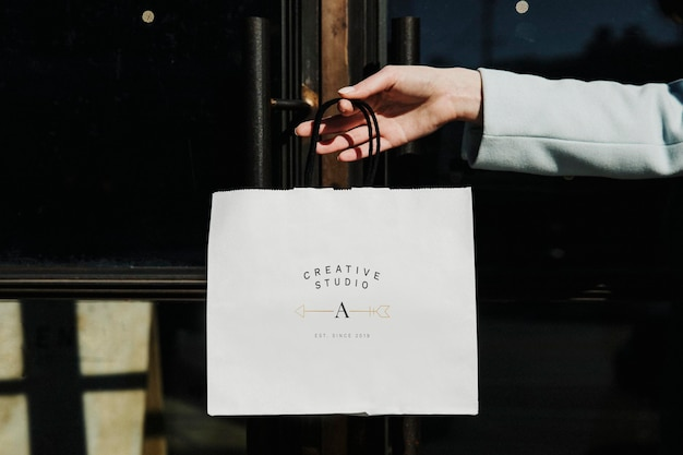 Hand hält eine einkaufstasche in der innenstadt