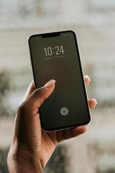 Hand hält smartphone am fenstermodell