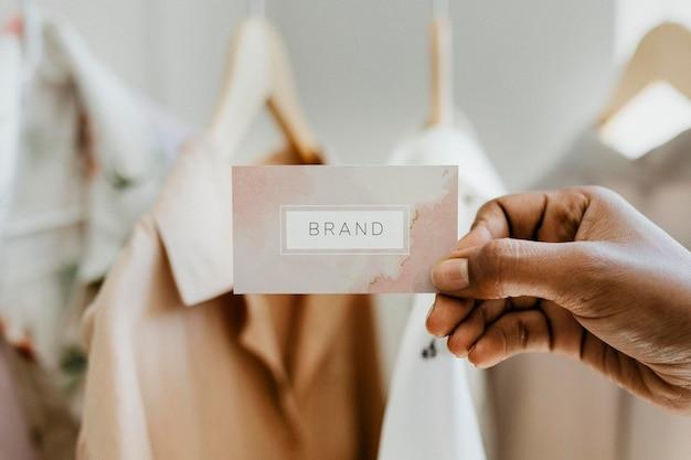 Hand hält visitenkarte in einer boutique