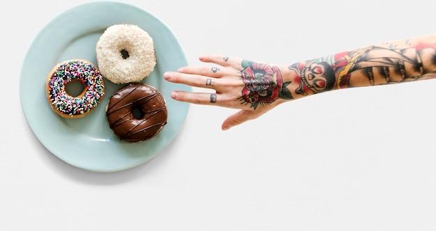 Hand mit tätowierung, die für donut erreicht