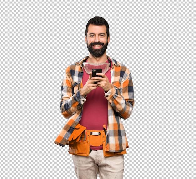 Handwerkermann, der eine mitteilung mit dem mobile sendet