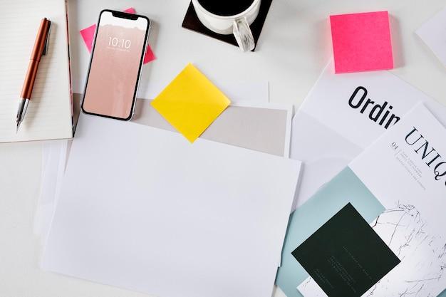Handy auf einem schreibtisch mit papiermodell