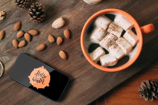 Handy mit hallo winter und köstlichem wintergetränk