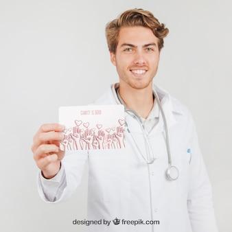 Happy doktor holding mock up