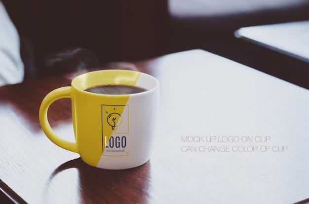 Heiße schwarze kaffeetasse auf hölzerner tischplatte am kaffeemodellmodell