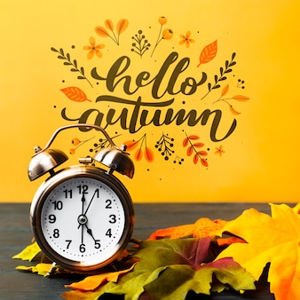 Herbstliche anordnung mit borduhr und blättern
