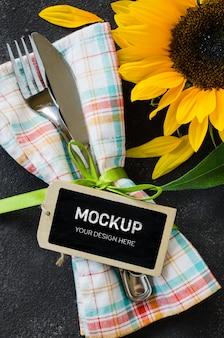 Herbsttischgedeck mit leerem etikett, besteck mit serviette und sonnenblume.