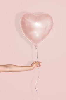 Herzförmiges ballonmodell auf rosa hintergrund