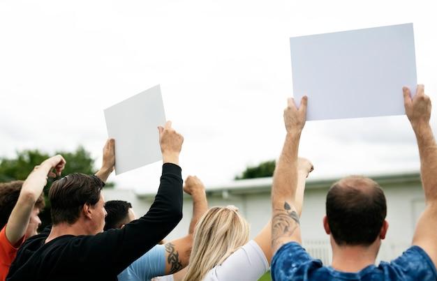 Hintere ansicht von den aktivisten, die papiere beim protest zeigen
