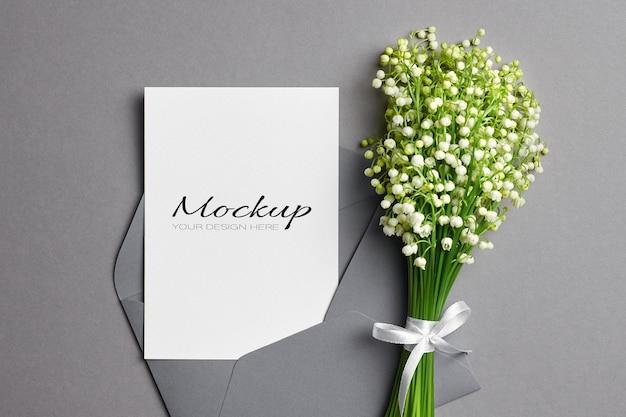 Hochzeitseinladung oder grußkartenmodell mit umschlag und maiglöckchenblumenstrauß