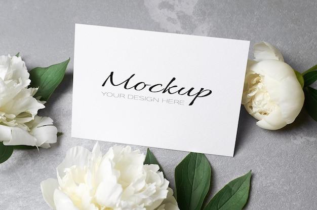 Hochzeitseinladung oder grußkartenmodell mit umschlag und weißen pfingstrosenblüten auf grau