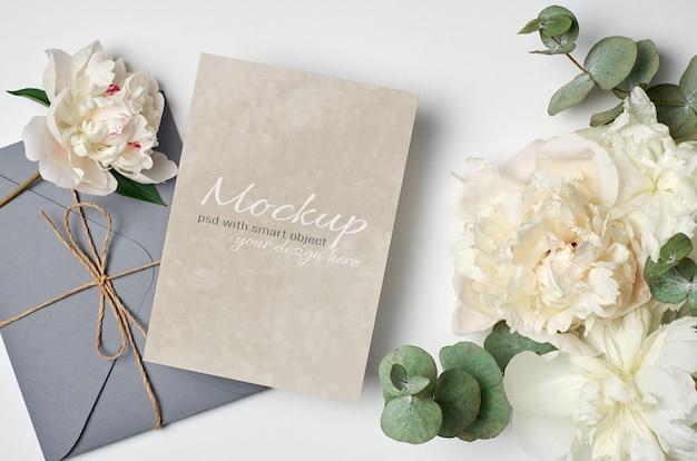 Hochzeitseinladung oder grußkartenmodell mit umschlag und weißen pfingstrosenblüten