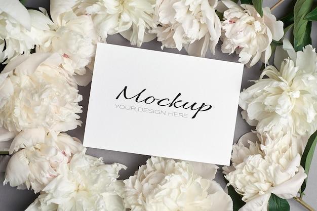 Hochzeitseinladung oder grußkartenmodell mit weißen pfingstrosenblüten auf grau