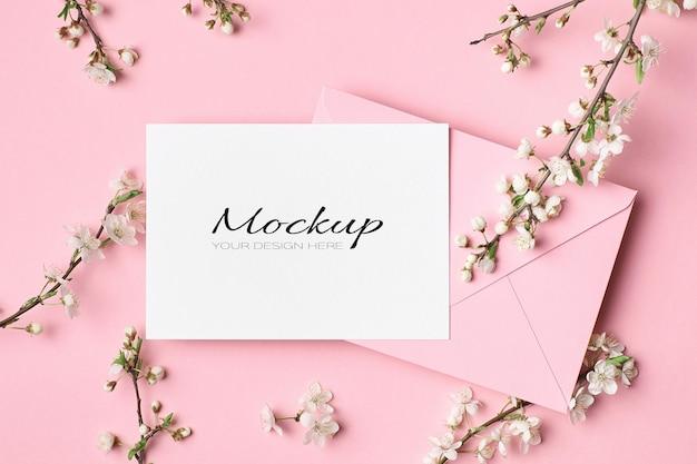 Hochzeitseinladungskartenmodell mit umschlag und frühlingsbaumzweigen mit blumen auf rosa
