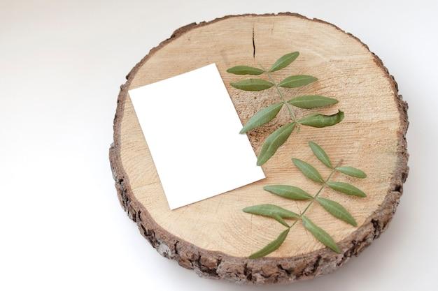Hochzeitskartenmodell auf einem hölzernen spucken mit blättern von pistazien