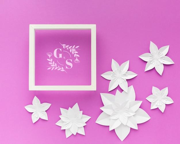 Hochzeitsrahmen mit papierblumen auf lila hintergrund