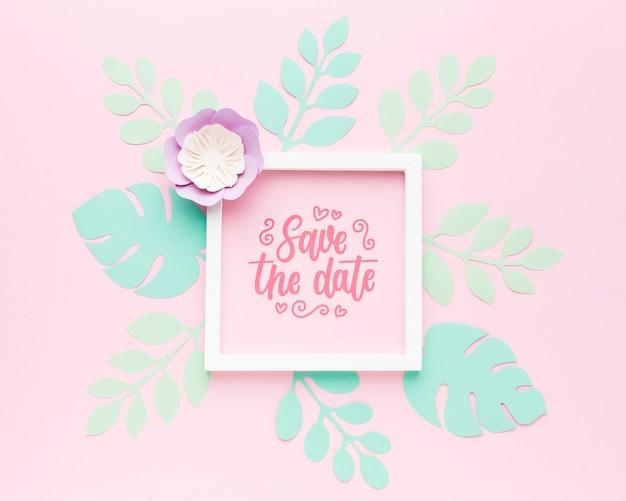 Hochzeitsrahmenmodell mit papierblättern auf rosa hintergrund