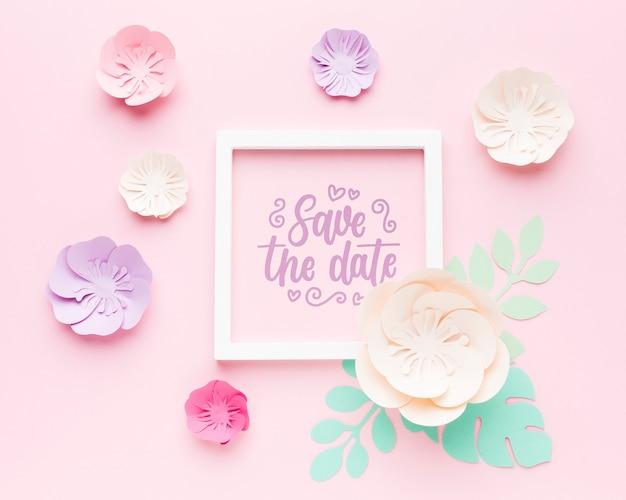 Hochzeitsrahmenmodell mit papierblumen auf rosa hintergrund