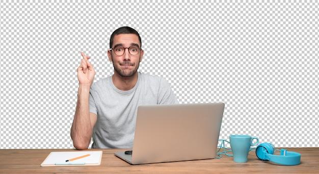 Hoffnungsvoller junger mann, der an seinem schreibtisch mit gekreuzter fingergeste sitzt