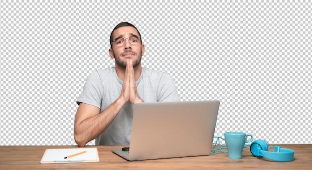 Hoffnungsvoller junger mann, der an seinem schreibtisch sitzt