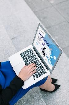 Hohe ansichtsfrau, die am laptop-modell arbeitet