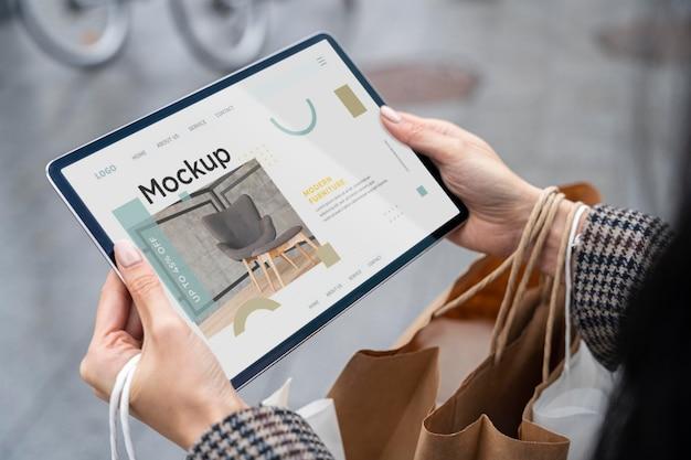 Hohe winkelfrau mit einkaufstaschen, die tablettenmodell halten