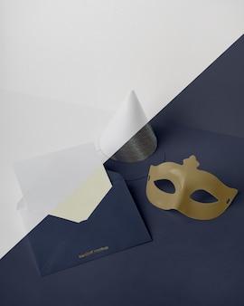 Hoher winkel der karnevalseinladung im umschlag mit kegel und maske