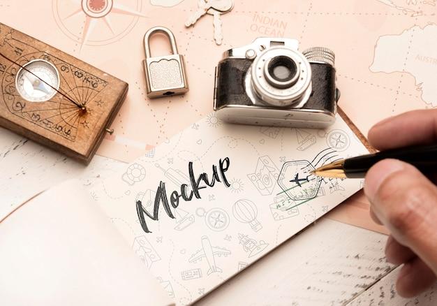 Hoher winkel der person, die auf papier mit kamera und kompass für das reisen schreibt