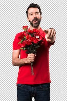 Holdingblumen des gutaussehenden mannes, die auf die front zeigen