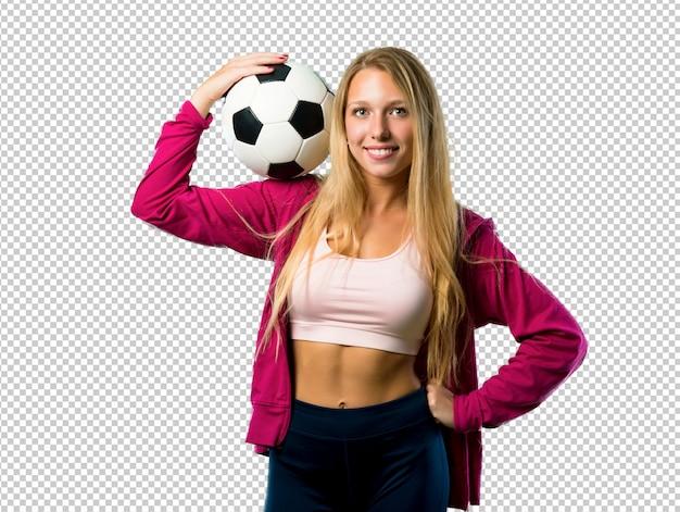 Hübsche sportfrau, die eine fußballkugel anhält