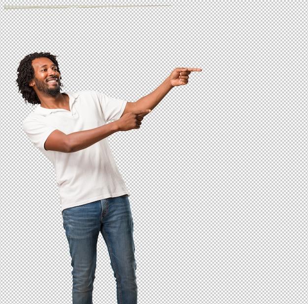 Hübscher afroamerikaner, der auf die seite, das lächeln überrascht zeigt, etwas darstellend, natürlich und zufällig
