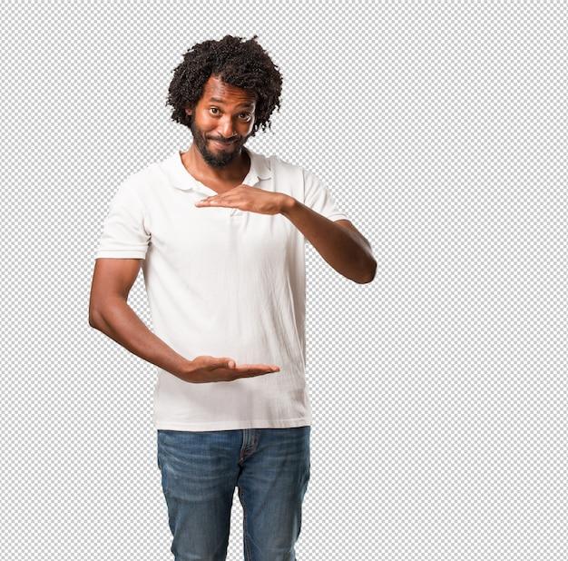 Hübscher afroamerikaner, der etwas mit den händen hält, ein produkt zeigt, lächelt und che