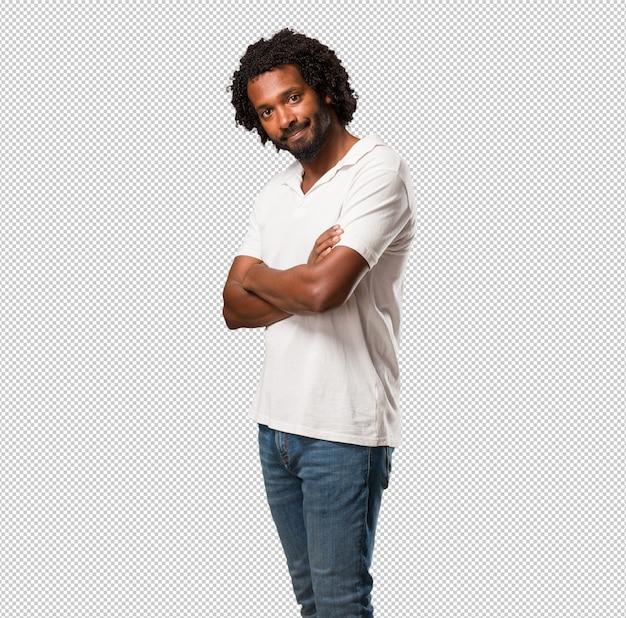 Hübscher afroamerikaner, der seine arme kreuzt, lächelt und glücklich, überzeugt und freundlich ist
