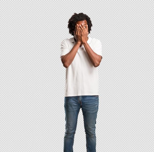 Hübscher afroamerikaner fühlt sich besorgt und erschrocken und schaut und bedeckt gesicht, konzept von furcht und angst