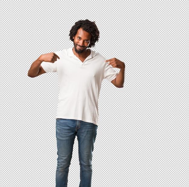 Hübscher afroamerikaner stolz und überzeugt, finger zeigend, um zu folgen, konzept der zufriedenheit, der arroganz und der gesundheit