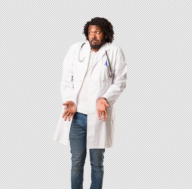 Hübscher afroamerikanerarzt, der die schultern, unentschlossenheit und unsicherheit bezweifelt und zuckt, unsicher über etwas