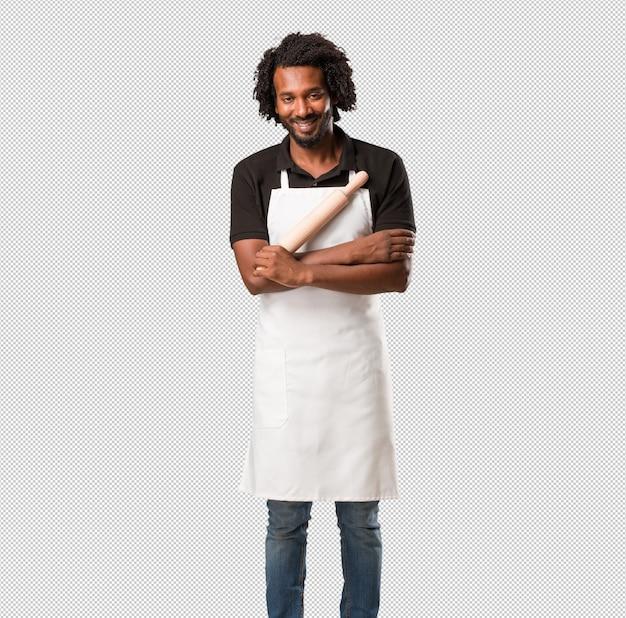 Hübscher afroamerikanerbäcker, der seine arme kreuzt, lächelt und glücklich ist, überzeugt und freundlich